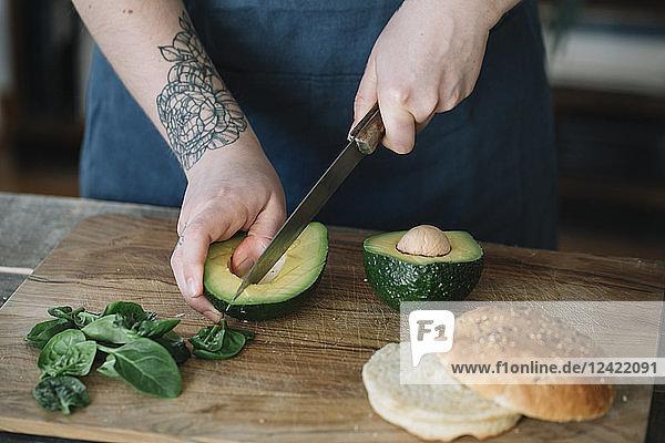 Woman preparing vegan burger  slicing avocado