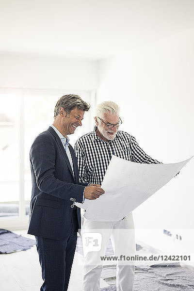 Happy man in suit and senior man looking at blueprint