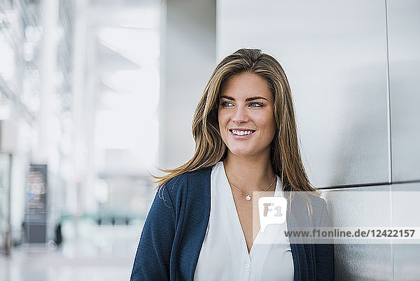 Portrait of smiling young businesswoman looking around