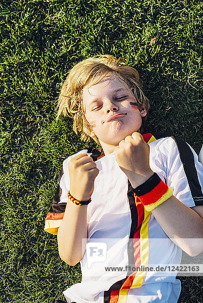 Boy in German soccer shirt lying on grass  keeping fingers crossed for world chamiponship