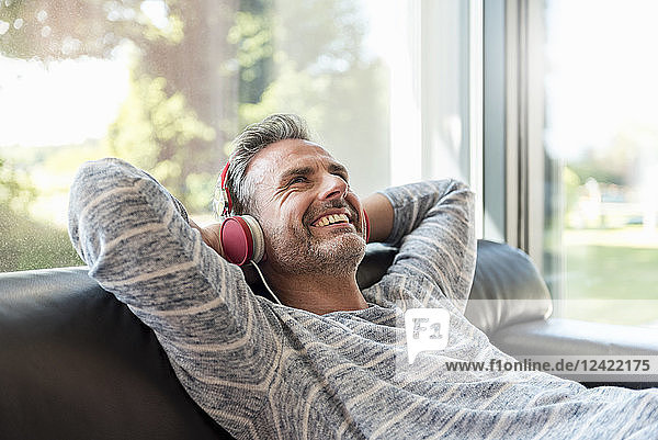 Happy mature man lying on couch at home wearing headphones
