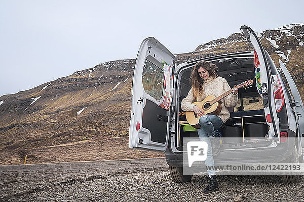 Iceland  woman in front of van playing guitar