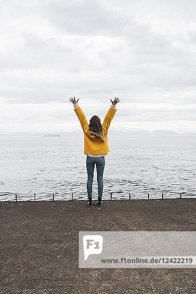 Iceland  woman standing at the sea with raised arms