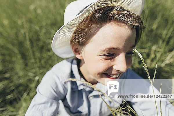 Happy boy wearing a hat sitting in field