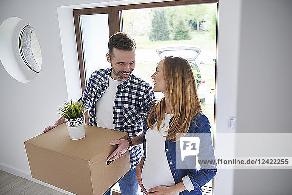 Happy man and pregnant woman moving into new flat carrying cardboard box