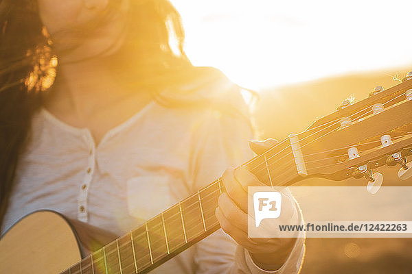 Iceland  woman playing guitar at sunset