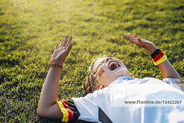 Boy in German soccer shirt lying on grass  laughing and screaming