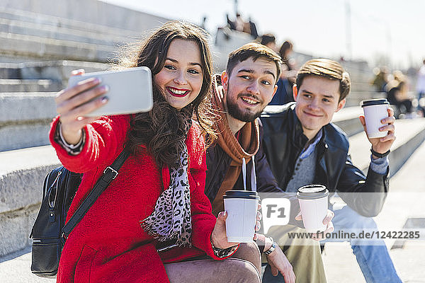 Russia  Moscow  group of friends taking a selfie and showing their cups of coffee