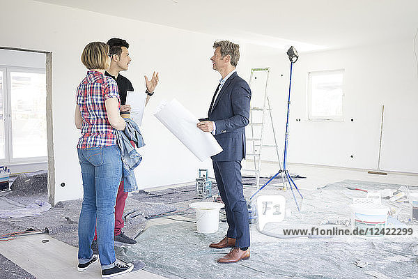 Man in suit talking to couple in unfinished building
