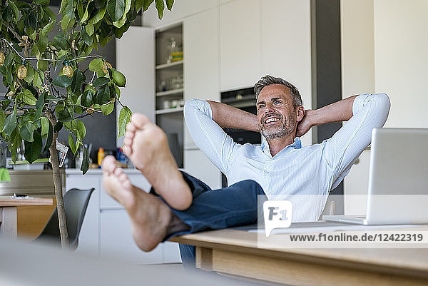 Smiling mature man relaxing at home with laptop on table