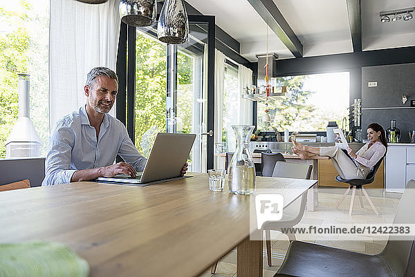 Smiling man at home using a laptop at table with woman in background reading newspaper