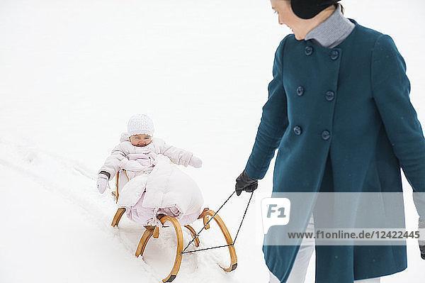 Mother pulling little daughter on sledge