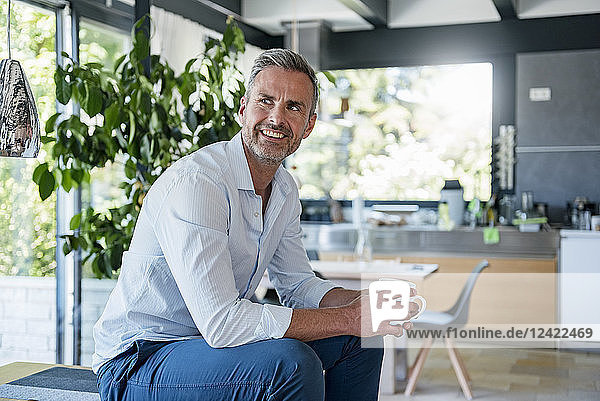 Smiling mature man at home sitting on table with cup of coffee