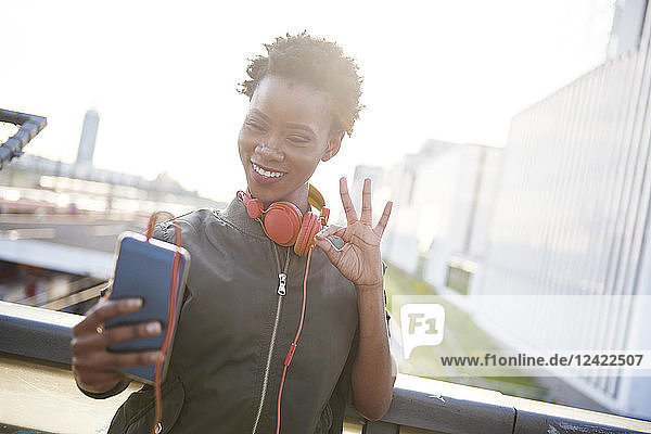 Portrait of young woman with headphones taking selfie with smartphone Portrait of young woman with headphones taking selfie with smartphone