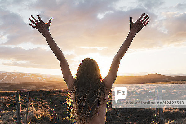 Iceland  young woman with raised arms at sunset