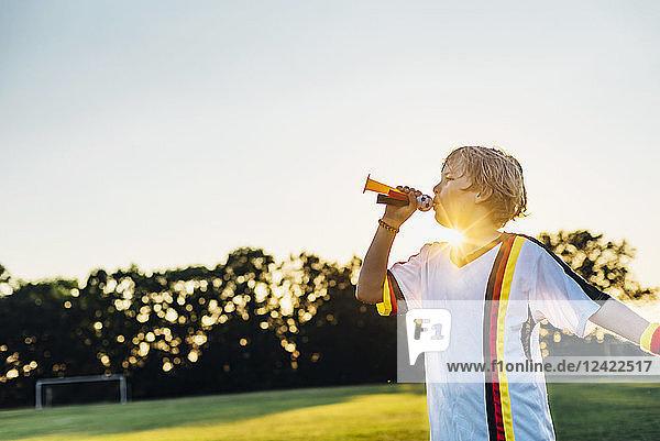 Boy wearing German soccer shirt  blowing horns on soccer field