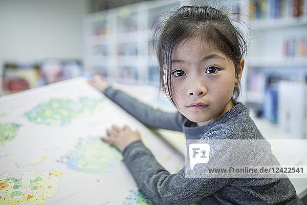 Portrait of schoolgirl with book in school