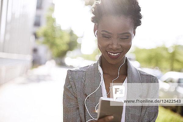 Portrait of smiling businesswoman using smartphone and earphones Portrait of smiling businesswoman using smartphone and earphones