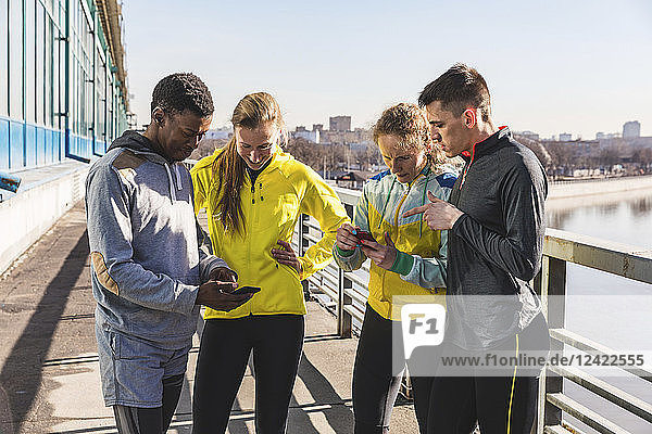 Sportive friends checking cell phones on a bridge in the city