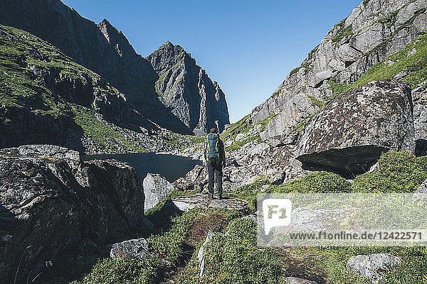 Norway  Lofoten  Moskenesoy  Young man standing in front of Litljordtinden