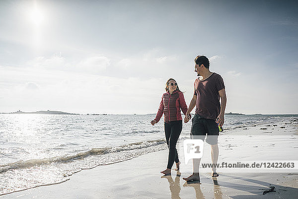 France  Brittany  Landeda  couple walking hand in hand on the beach