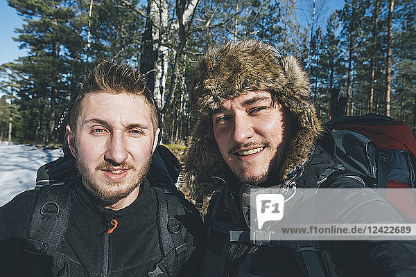 Sweden  Sodermanland  portrait of two smiling men in remote landscape in winter