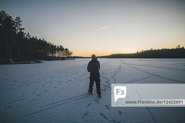 Sweden  Sodermanland  man walking on frozen lake Navsjon in winter