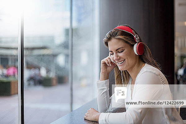Happy young woman listening to music with headphones