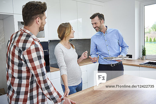 Couple and real estate agent talking in kitchen of new apartment Couple and real estate agent talking in kitchen of new apartment
