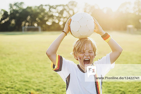 Boy wearing German soccer shirt screaming for joy