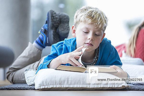 Schoolboy lying on the floor reading book in school break room