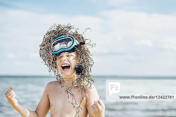 Carefree boy wearing seaweed wig on the beach