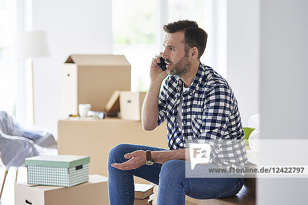 Serious man moving into new flat talking on cell phone