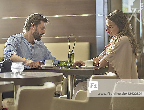 Man and woman sitting at table drinking coffee