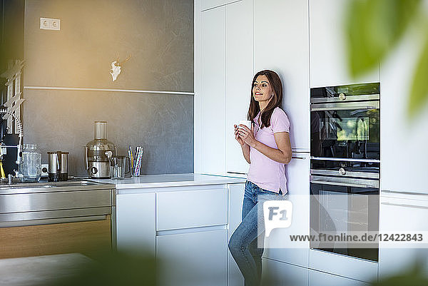 Smiling woman at home in kitchen with cup of coffee