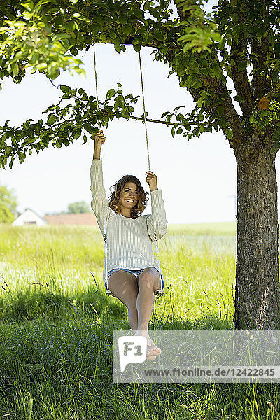 Smiling young woman sitting on swing