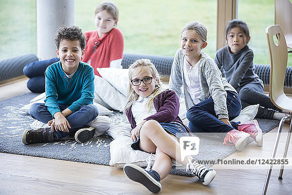 Portrait of smiling pupils sitting on the floor in school break room