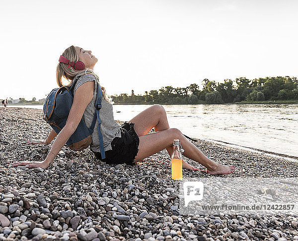 Blond woman with earphone and bottle sitting on riverside in the evening  listening music