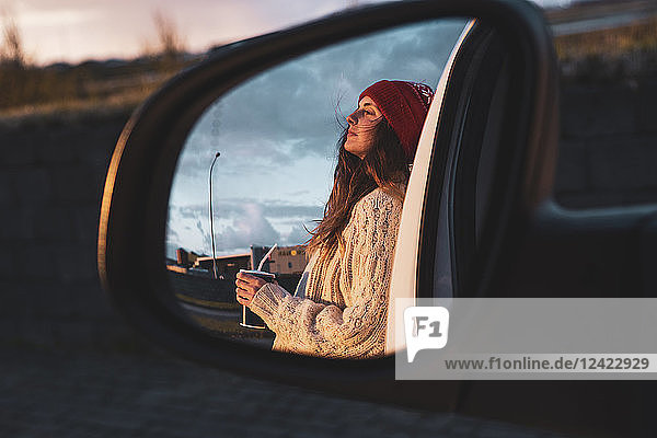 Iceland  young woman with coffee to go at sunset  mirrored in wing mirror