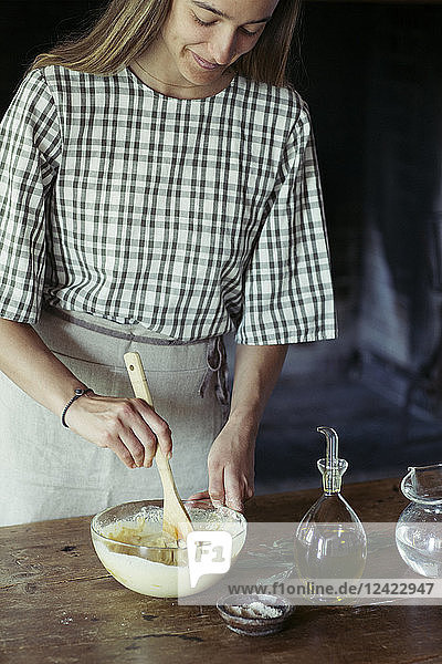 Young woman in kitchen preparing dough for fresh chickpea cake