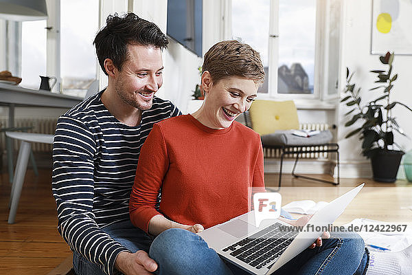 Couple sitting cross-legged on floor of their home  using laptop