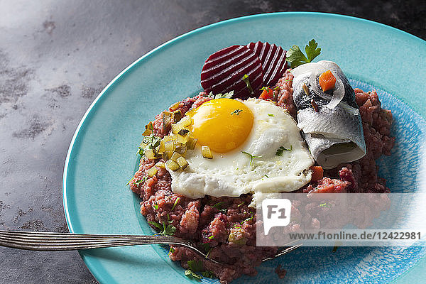 Plate of Labskaus with potatoes  rollmops  pickled gherkin  beetroot and fried egg