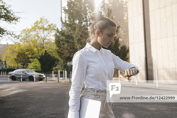 Young businesswoman carrying laptop  checking the time