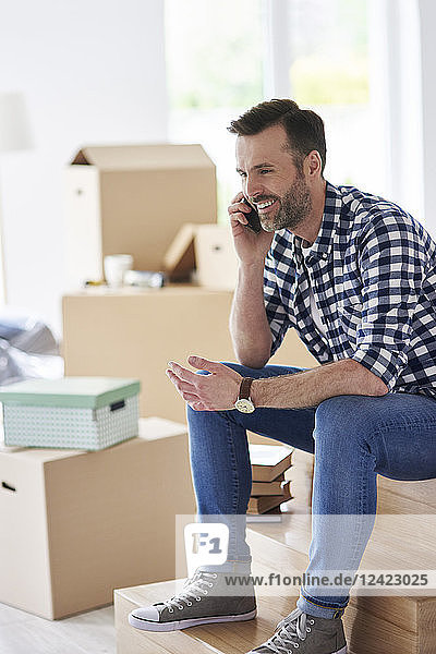 Smiling man moving into new flat talking on cell phone