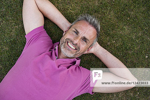 Portrait of smiling mature man lying in grass