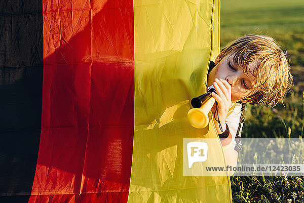 Boy standing behind German flag  blowing horns for soccer world championship