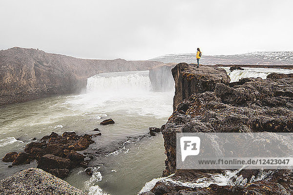 Iceland  woman standing at Godafoss waterfall