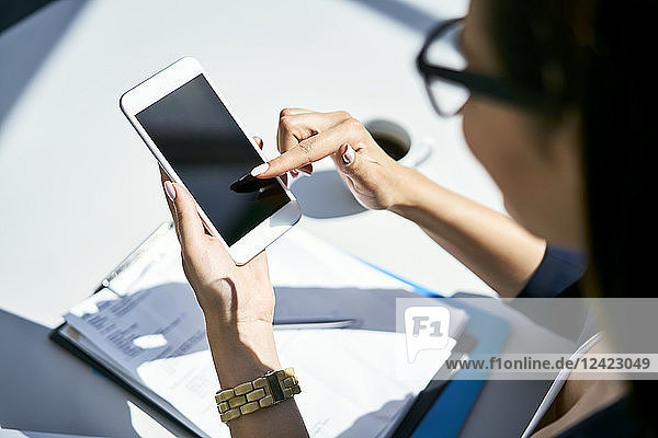 Close-up of businesswoman using cell phone at desk in office