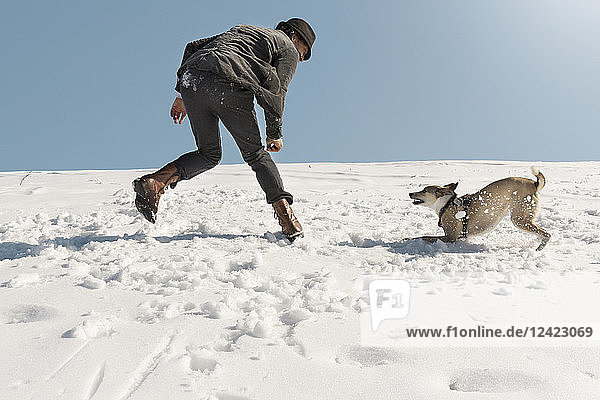 Man playing with dog in winter  throwing snow