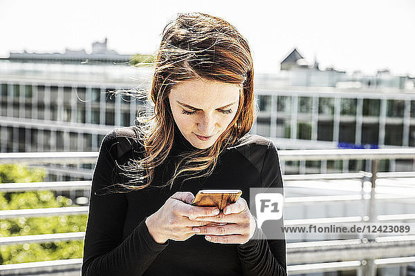 Woman text messaging on roof terrace